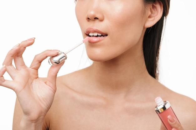 Retrato recortado de uma jovem e bela mulher asiática posando isolado na parede branca, segurando o brilho labial de batom de maquiagem