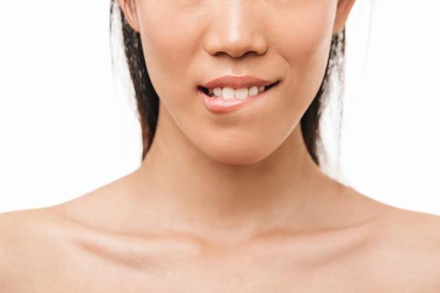 Retrato recortado de uma jovem e bela mulher asiática posando isolado sobre o lábio de mordida de parede branca