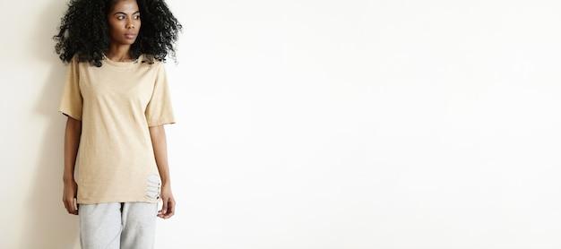 Retrato recortado de uma jovem modelo africana atraente e elegante, com cabelo encaracolado posando dentro de casa, olhando para longe com uma expressão facial séria