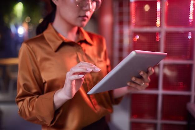 Retrato recortado de uma mulher de negócios asiática contemporânea usando tablet digital enquanto trabalhava no interior de um escritório futurista