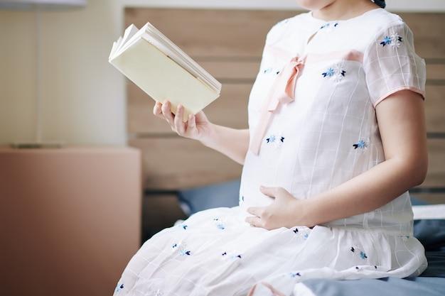 Retrato recortado de uma mulher grávida com um vestido de verão, sentada na cama em casa, lendo um livro