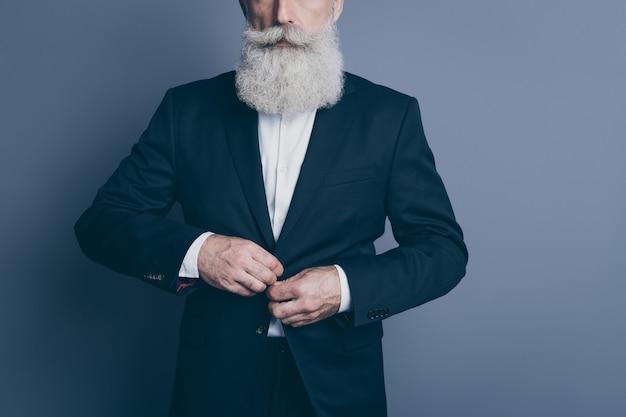 Retrato recortado dele, ele agradável atraente chique elegante calmo homem de cabelos grisalhos usando um botão de fecho de smoking vestindo roupas formais isoladas sobre fundo cinza escuro pastel