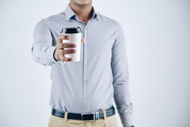 Retrato recortado do empresário estendendo a mão com uma xícara de café para viagem, isolado no branco