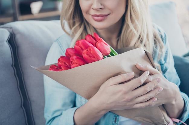Retrato recortado em close-up de uma mulher sonhadora sentada no divã segurando uma flor