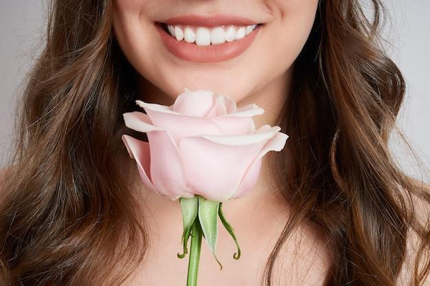 Retrato recortado em close-up de uma mulher sorridente com uma rosa rosa perto do rosto