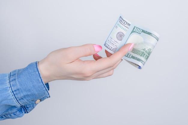 Retrato recortado em close-up do perfil lateral de mãos segurando mostrando cem dólares isolados sobre uma parede cinza