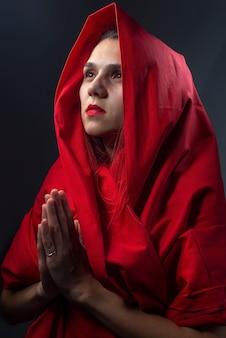 Retrato religioso dramático menina de vermelho reza com as mãos postas.