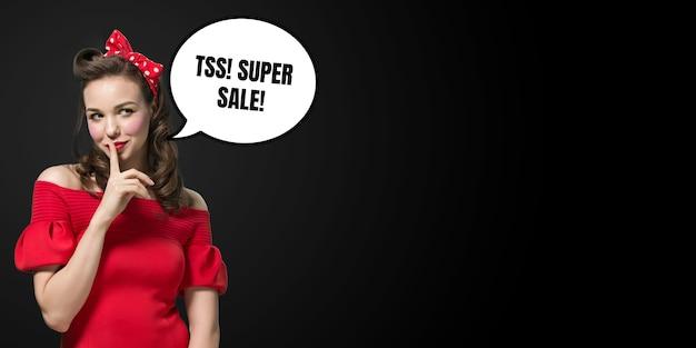 Retrato retrô de mulher com balão em fundo preto. copyspace para sua publicidade. black friday, cyber segunda-feira, vendas, dinheiro e dinheiro, compras e pagamentos online. manter segredo.