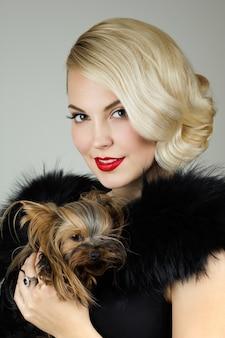 Retrato retrô de uma linda mulher segurando o yorkshire terrier