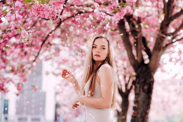 Retrato romântico da loira encantadora na parede de um jardim florescendo. árvore com flores cor de rosa. mulher loira de beleza com cabelos longos ao ar livre. flores de cerejeira. feche o retrato. sakura