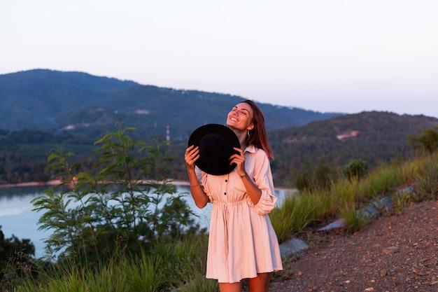 Retrato romântico de jovem caucasiana com vestido de verão relaxando no parque na montanha com vista para o mar tropical
