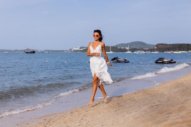 Retrato romântico de mulher bronzeada com vestido branco de verão na praia tropical ao pôr do sol