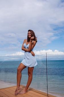 Retrato romântico de mulher com vestido azul claro sozinha em uma praia tropical, dia de sol, pele morena bronzeada
