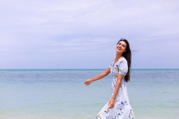 Retrato romântico de mulher com vestido longo azul na praia à beira-mar em dia de vento
