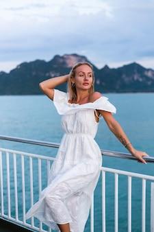 Retrato romântico de mulher de vestido branco navegando em uma grande balsa