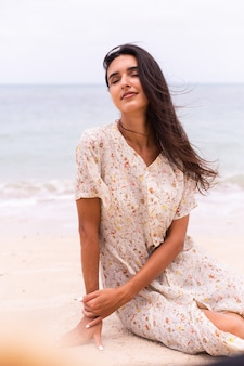 Retrato romântico de mulher em um vestido longo na praia em dia nublado com vento.