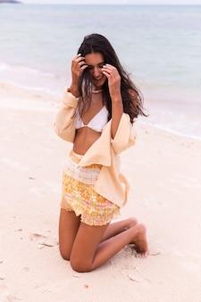 Retrato romântico de mulher na praia em dia de vento, luz quente do sol.