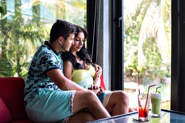 Retrato romântico de um jovem casal bonito posando em um café elegante, bebendo coquetéis e um abraço, clima de encontro perfeito.