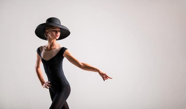Retrato romântico de uma linda jovem em um fundo claro com um chapéu elegante apontando para a direita