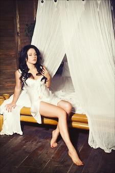 Retrato romântico de uma linda jovem morena de lingerie branca em um bangalô tropical
