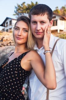 Retrato romântico de verão de um lindo casal se abraçando perto do mar