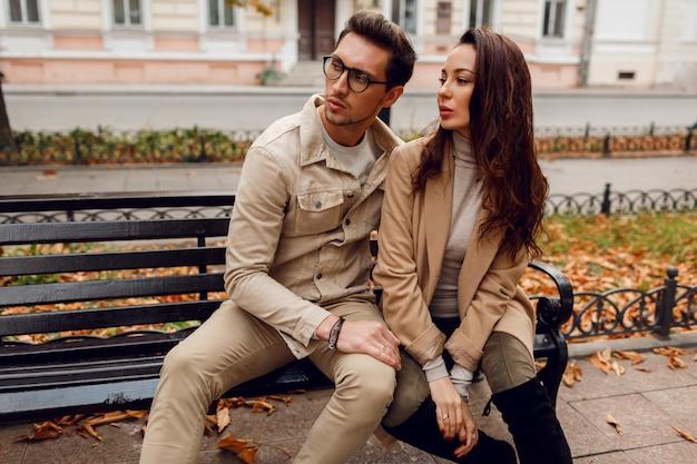 Retrato romântico do jovem casal lindo amor, abraçando e beijando no banco no parque outono. vestindo casaco bege elegante.