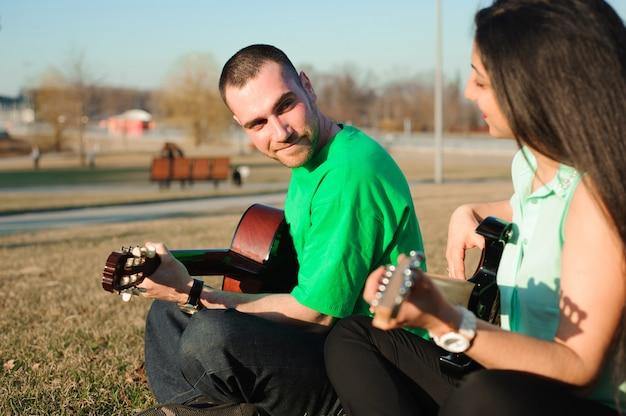 Retrato romântico jovem casal tocando violão sob o céu azul
