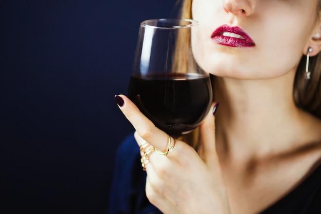Retrato sem rosto de jovem adulto branco com batom de ameixa escuro, segurando um copo de vinho tinto na mão. .