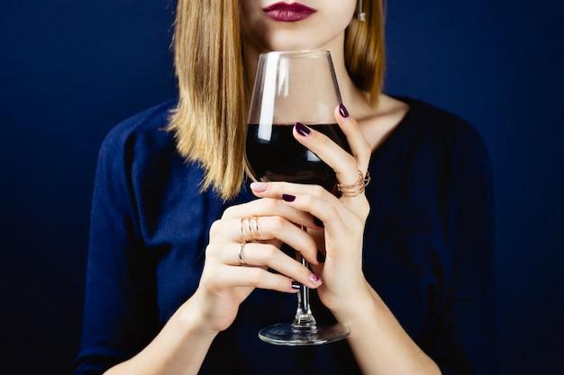Retrato sem rosto de jovem adulto branco com batom de ameixa escuro, segurando um copo de vinho tinto nas mãos dela. .