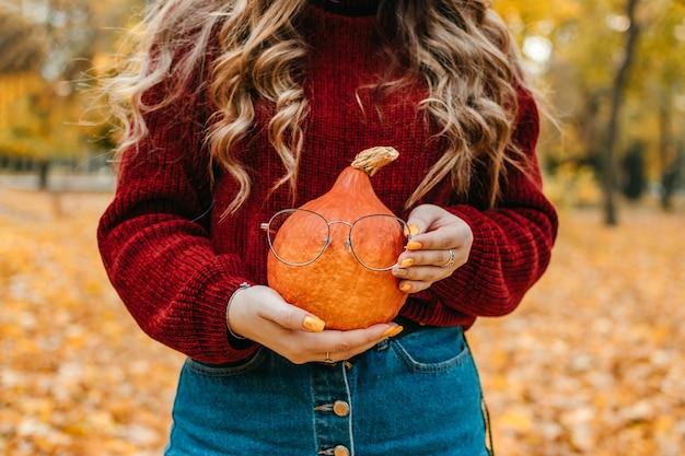 Retrato sem rosto de mulher segurando abóbora laranja de halloween no fundo de árvores amarelas do parque outono