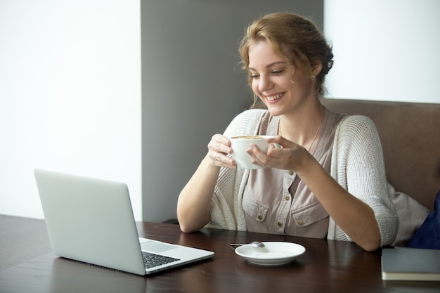 Retrato semi-comprimento da mulher de negócios na pausa para café no café