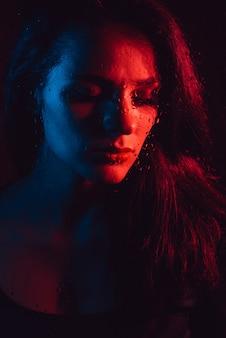 Retrato sensual da menina triste através do vidro com pingos de chuva com iluminação azul vermelha