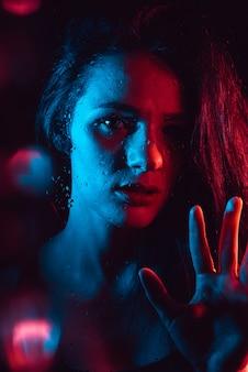 Retrato sensual de uma linda garota atraente, olhando através do vidro com pingos de chuva