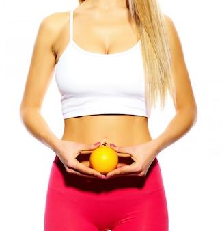 Retrato sensual do esporte bonito jovem fitness mulher menina com corpo perfeito witn laranja