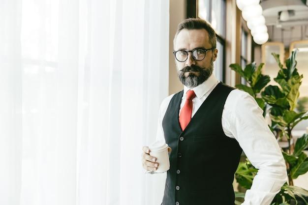 Retrato sério profissional conservador adulto modelo empresário latino barba em pé mão segurando a xícara de café em um escritório moderno, com espaço de cópia para o texto.