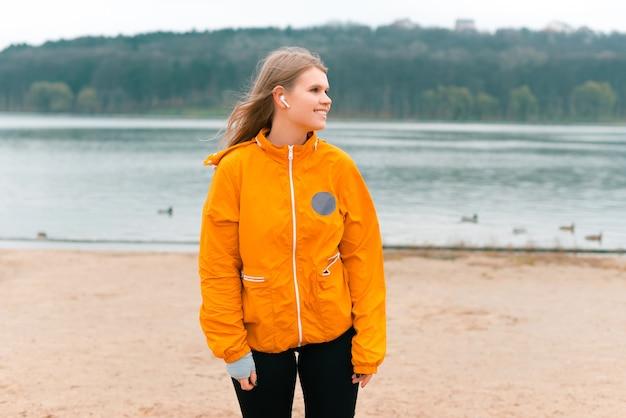 Retrato simples de uma jovem vestindo roupas esportivas, em pé perto de um lago.