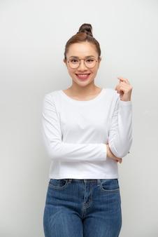 Retrato simples de uma menina asiática com os braços cruzados na parede branca.