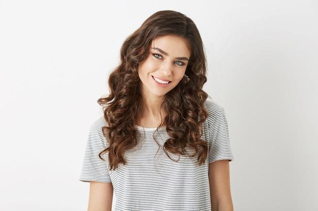 Retrato simples em close-up de mulher jovem e atraente com cabelo encaracolado sorrindo isolado, vestida com camiseta, estilo casaual, aparência natural