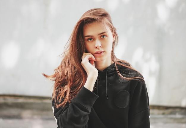 Retrato sincero de hipster de modelo de moda jovem garota cabelos longos bonitos com capuz preto
