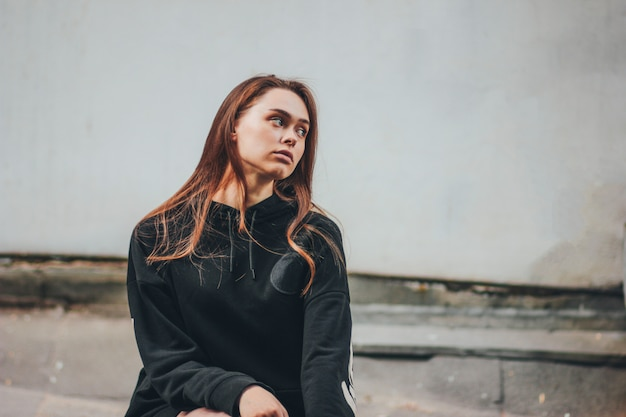 Retrato sincero de hipster de modelo de moda jovem infeliz menina de cabelos longos com capuz preto