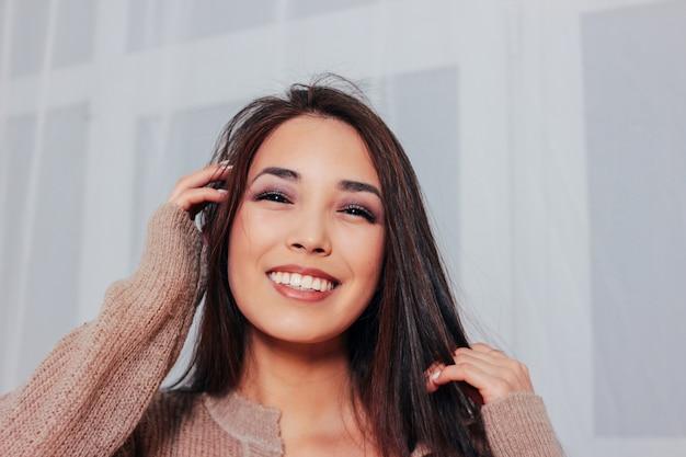 Retrato sincero de sensual sorridente menina asiática jovem com cabelos longos escuros na camisola bege acolhedor
