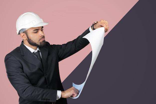Retrato sorridente confiante do arquiteto preto segurando planos isolados no estúdio