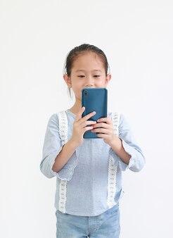 Retrato sorridente criança asiática usando smartphone isolado no branco