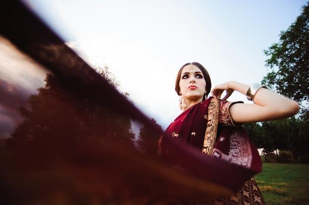 Retrato sorridente da bela garota indiana. modelo jovem indiano com conjunto de jóias vermelho