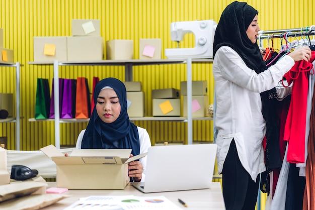 Retrato sorridente de lindos proprietários muçulmanos trabalhando em um laptop com caixas de pacotes na mesa em casa