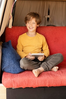 Retrato sorridente de menino usando tablet