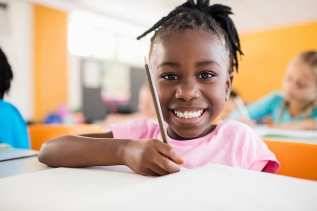 Retrato sorridente de um aluno estudando