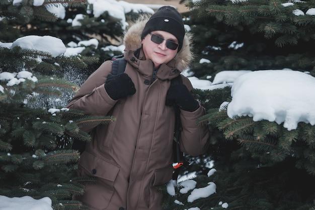 Retrato sorridente jovem brutal ao ar livre entre árvores de natal cobertas de neve no inverno na floresta. turista com óculos e mochila se perdeu em uma área desconhecida. caminhadas loucas de adolescentes