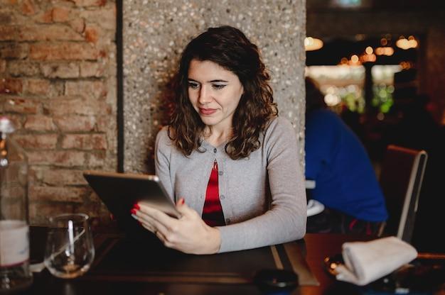 Retrato sorridente jovem caucasiana em um restaurante segurando um tablet.