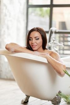 Retrato sorridente linda fêmea relaxante no banho